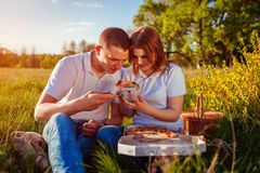 Young couple eating pizza outside and checking selfie photo. Woman and man having picnic at sunset. Guys having fun. royalty free stock photos