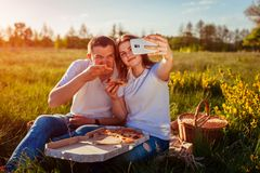 Young couple eating pizza outside and taking selfie. Woman and man having picnic at sunset. Guys having fun. royalty free stock image