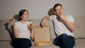 Young couple eating pizza. Drinking, talking and smiling at the home stock video