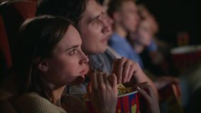 Young couple eating popcorn from one box. Fiends couple watching movie stock video