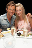 Young couple eating in restaurant. Smiling to camera Stock Photos