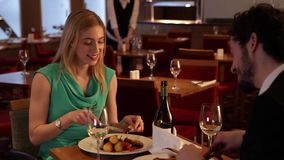 Young couple eating in a restaurant stock footage