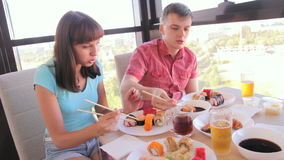 Young couple eating rolls with chopsticks, Asian food stock footage