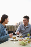 Young couple eating on the roof top, smiling and looking at each other Stock Images