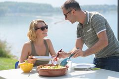 Young couple eating salad near lake during summer Royalty Free Stock Photo