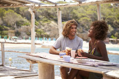 Young couple eating at a table by the sea look at each other Royalty Free Stock Images