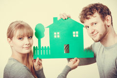 Young couple with ecological green house. Ecology in practical domestic life. People real estate and house concept. Young couple with green ecological paper royalty free stock image