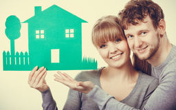 Young couple with ecological green house. Ecology in practical domestic life. People real estate and house concept. Young couple with green ecological paper stock image