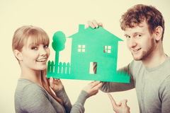 Young couple with ecological green house. Ecology in practical domestic life. People real estate and house concept. Young couple with green ecological paper stock photos