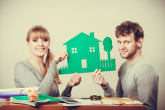 Young couple with ecological green house. Ecology in practical domestic life. People real estate and house concept. Young couple with green ecological paper royalty free stock images