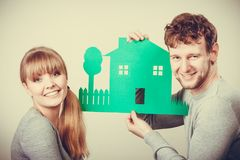 Young couple with ecological green house. Ecology in practical domestic life. People real estate and house concept. Young couple with green ecological paper stock photography