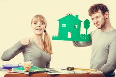Young couple with ecological green house. Ecology in practical domestic life. People real estate and house concept. Young couple with green ecological paper royalty free stock photography
