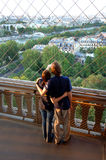 Young couple on Eiffel tower. A back view of young couple with arms around each other pointing while taking in the view of Paris from on the Eiffel Tower stock photos