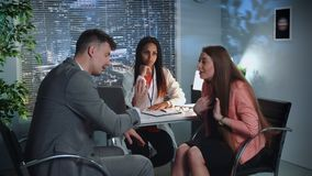 Young couple in elegant dresses quarreling with each other at the therapy session. Mixed race psychologist listening to them and writing notes stock video