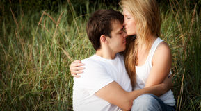 Young couple embrace. In high grass Stock Photo