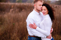 Young couple embrace in autumnal landscapes with closed eyes, wh. Ite dress Royalty Free Stock Images