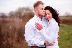 Young couple embrace in autumnal landscapes with closed eyes, wh. Ite dress Royalty Free Stock Photo