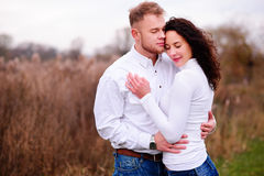 Young couple embrace in autumnal landscapes with closed eyes, wh. Ite dress Stock Images