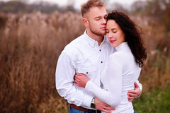 Young couple embrace in autumnal landscapes with closed eyes, wh. Ite dress Royalty Free Stock Photography