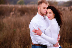Young couple embrace in autumnal landscapes with closed eyes, wh. Ite dress Stock Photo