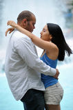 Young couple embrace in front of fountain. Young couple - Asian woman and biracial male - embrace and look into each others eyes in front of a city fountain Stock Photos