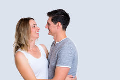 Young couple in an embrace. In front of gray background Royalty Free Stock Image