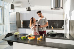Young Couple Embrace In Kitchen, Hispanic Man And Asian Woman Hug Drink Wine. Modern Apartment Interior Stock Photo
