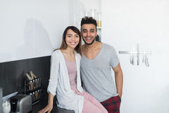 Young Couple Embrace In Kitchen, Hispanic Man And Asian Woman Hug. Modern Apartment Interior Stock Photo