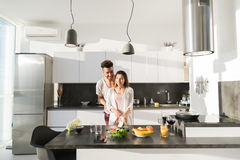 Young Couple Embrace In Kitchen, Hispanic Man And Asian Woman Hug. Modern Apartment Interior Royalty Free Stock Photography