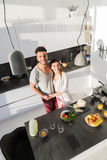 Young Couple Embrace In Kitchen, Hispanic Man And Asian Woman Hug Top Angle View. Modern Apartment Interior Royalty Free Stock Photos