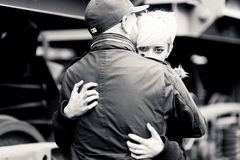 Young couple embrace one another over freight trai. Black and white outdoors picture of young caucasian casual couple embracing one another over freight train Royalty Free Stock Images