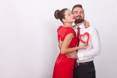 Young couple embrace with pleasure, closed eyes. Indoor, studio shot,  on gray background Stock Photo