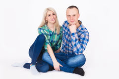 Young couple in an embrace sitting on the floor in a studio. Young couple in an embrace sitting on the floor in a studio on a white background Royalty Free Stock Image