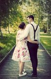 Young couple embrace while standing on wooden path Stock Photo