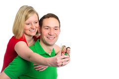 Young couple in an embrace take selfie. Young couple in an embrace in front of white background take selfie Stock Photos