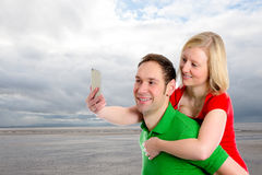 Young couple in an embrace take selfie. In front of wideness Stock Image