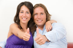 Young couple embraced with thumbs up Stock Photo