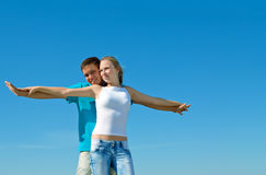 Young couple embracing against blue sky Stock Photography