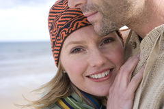 Young couple embracing on beach, close-up of woman smiling, portrait Stock Photo