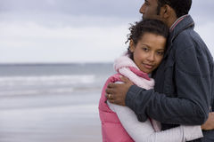 Young couple embracing on beach, portrait of woman Stock Photography