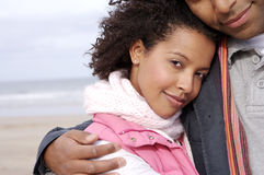 Young couple embracing on beach, portrait of woman Royalty Free Stock Photos