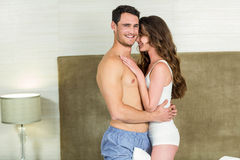 Young couple embracing in bedroom Stock Images