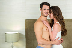 Young couple embracing in bedroom Stock Photography