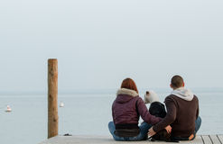 Young couple embracing dog looking at sea Stock Photos