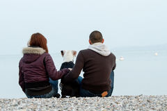 Young couple embracing dog looking at sea Royalty Free Stock Photo