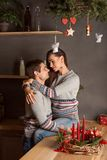 Young couple embracing gently and passionately kissing in the kitchen under the mistletoe on Christmas new year royalty free stock photography