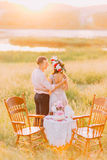 Young couple embracing and holding hands near table decorated wiht cake, bottles, candles, textile, pink flowers in rural field at Royalty Free Stock Photography