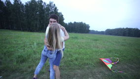Young couple embracing and kissing on summer field stock video footage