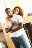 Young Couple Embracing In Living Room Royalty Free Stock Photography