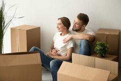 Young couple embracing looking forward to future in new home. After moving in relocation, happy smiling men and women homeowners holding hands dreaming of Stock Photo